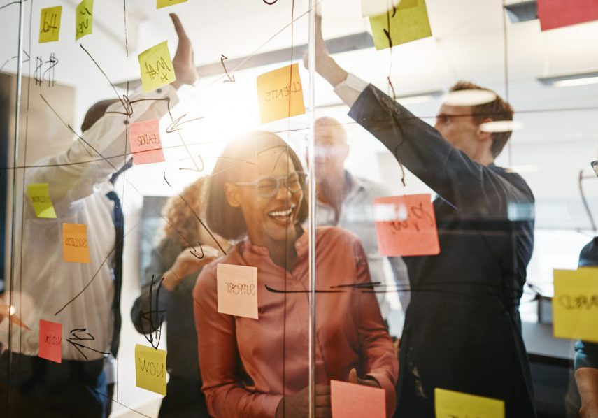Diverse group of ecstatic businesspeople celebrating a winning idea together while brainstorming on a glass wall in a modern office